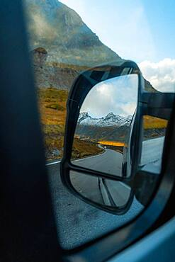 View of the fjord landscape through Campervan side mirror, Ramberg, Lofoten, Norway, Europe