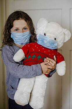 Girl and teddy bear with mouth mask