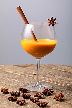 Orange fruity cocktail with cinnamon stick and star anise in a glass, on a wooden table