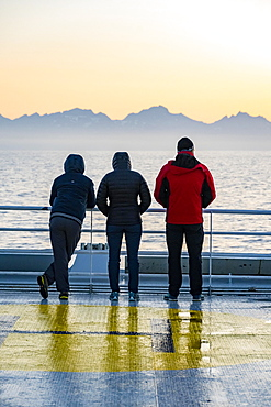Passengers looking over the ocean, evening mood on the ferry in front of silhouette of mountains, Lofoten, Nordland, Norway, Europe