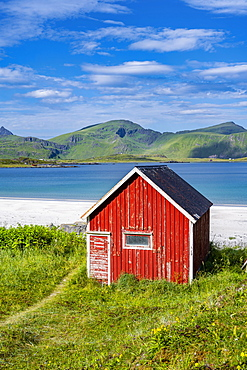 Rorbuer, traditional wooden house on sandy beach Rambergstranda, mountains and sea, Junesvika, Lofoten, Nordland, Norway, Europe