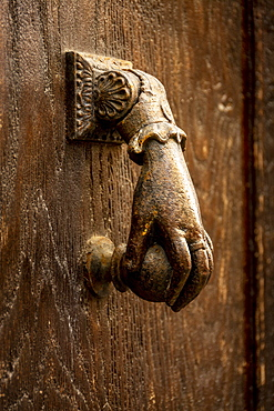 Knocker shaped like a hand on a wooden door, France, Europe