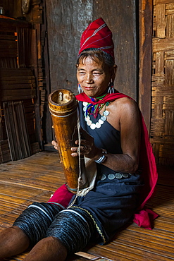 Old Kayah woman playing local instrument, Kayah village, Loikaw area, Kayah state, Myanmar, Asia