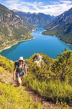 Hiker walking at Plansee, mountains with lake, Ammergau Alps, district Reutte, Tyrol, Austria, Europe