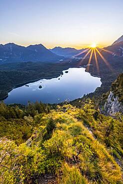 Eibsee lake at sunrise, sun shining over Bavarian alpine foothills, right Zugspitze, Wetterstein mountains near Grainau, Upper Bavaria, Bavaria, Germany, Europe