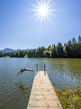 Young woman taking a header into a lake, Geroldsee, Mittenwald, Karwendel, Bavaria, Germany, Europe