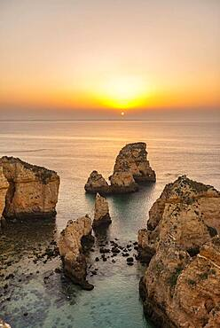 Rugged rocky coast with cliffs of sandstone, rock formations in the sea, Ponta da Piedade, dawn at sunrise, Algarve, Lagos, Portugal, Europe