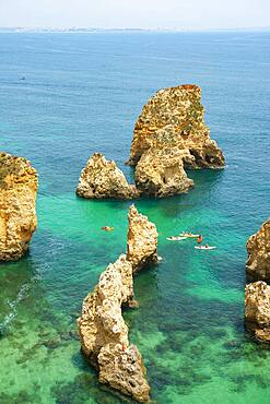 SUPs in the turquoise sea between rock formations, Rugged rocky coast with cliffs of sandstone, Ponta da Piedade, Algarve, Lagos, Portugal, Europe