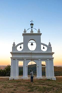 Bell ringer ringing the bells at the bell tower of the chapel Ermita Reina de los Angeles, at sunset, Alajar, Huelva, Spain, Europe