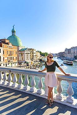 Young woman leaning against bridge railing on the Grand Canal, Church of San Simeone Piccolo, Ponte degli Scalzi, Venice, Veneto, Italy, Europe