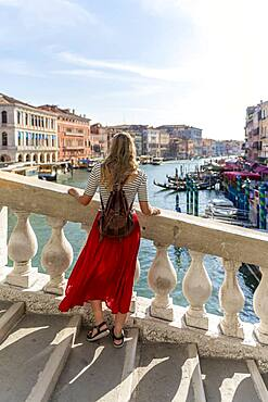 Young woman with red skirt walks over a bridge at the Grand Canal, Rialto Bridge, Venice, Veneto, Italy, Europe