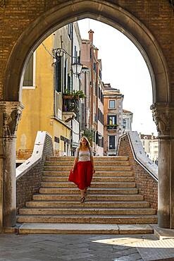 Young woman with red skirt walks through archway, Mercato di Rialto, Venice, Veneto, Italy, Europe