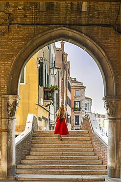 Young woman with red skirt on stairs, archway, Mercato di Rialto, Venice, Veneto, Italy, Europe