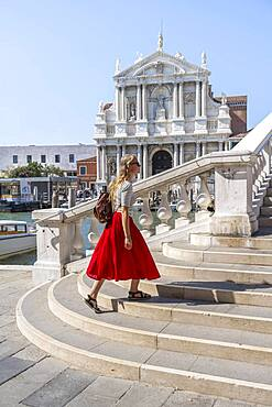Young woman with red skirt walks over a bridge at the Grand Canal, Church of Santa Maria di Nazareth, Ponte degli Scalzi, Venice, Veneto, Italy, Europe