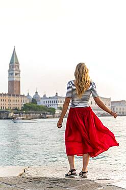 Young woman with red skirt standing on the waterfront, view of Venice and the Campanile bell tower, Venice, Veneto, Italy, Europe