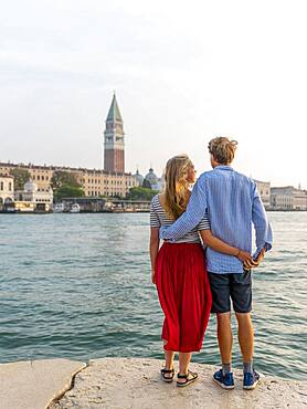 Young couple standing by the sea enjoying view of St. Mark's Square with Campanile di San Marco, Venice, Veneto, Italy, Europe