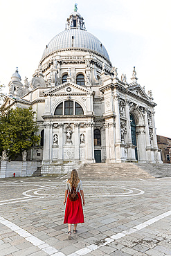 Young woman with red dress in front of church, Basilica di Santa Maria della Salute, Venice, Veneto, Italy, Europe