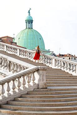 Young woman with red skirt walks over a bridge at the Grand Canal, church San Simeone Piccolo, Ponte degli Scalzi, Venice, Veneto, Italy, Europe