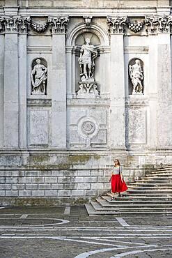 Young woman with red dress in front of white church, Basilica di Santa Maria della Salute, Venice, Veneto, Italy, Europe