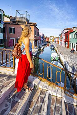 Young woman in front of colorful houses, canal with boats and colorful house facades, Burano Island, Venice, Veneto, Italy, Europe