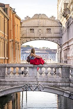 Young woman with red skirt, tourist sitting on a bridge railing, bridge over the Rio di Palazzo, behind Bridge of Sighs, Venice, Veneto, Italy, Europe