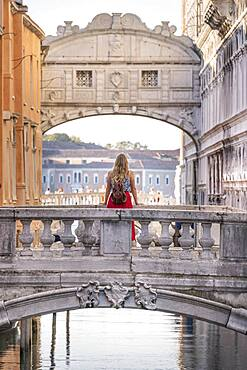 Young woman with red skirt, tourist leaning on bridge railing, bridge over Rio di Palazzo, behind Bridge of Sighs, Venice, Veneto, Italy, Europe