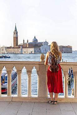 Young woman tourist sitting by the sea looking at the church Chiesa di San Giorgio Maggiore, Venice, Veneto, Italy, Europe