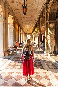 Young woman tourist walking under arcades at St. Mark's Square, Venice, Veneto, Italy, Europe