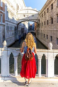 Young woman with red skirt, tourist on a bridge over the Rio di Palazzo, behind Bridge of Sighs, Venice, Veneto, Italy, Europe
