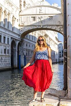 Young woman with red skirt, tourist at the canal Rio di Palazzo, behind Bridge of Sighs, Venice, Veneto, Italy, Europe