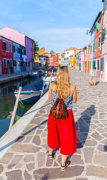 Woman walking past colorful houses, canal with boats and colorful house facades, Burano Island, Venice, Veneto, Italy, Europe
