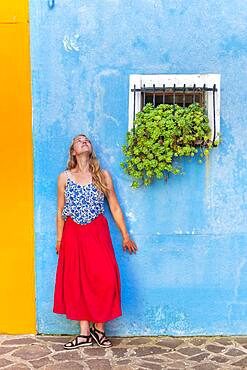 Young woman in front of blue house, colorful house facades, Burano Island, Venice, Veneto, Italy, Europe