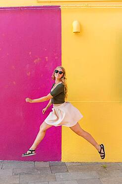 Young woman in dress jumps happily in front of colorful house, yellow and pink house facade, Burano Island, Venice, Veneto, Italy, Europe