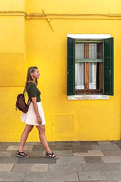 Young woman walking in front of colorful house, yellow house facade, tourist on Burano island, Venice, Veneto, Italy, Europe