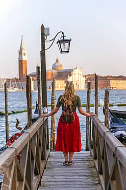 Young woman with red dress on a jetty, behind church San Giorgio Maggiore, Venice, Veneto, Italy, Europe