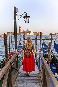 Young woman with red dress on a jetty, Venetian gondolas, in the back church San Giorgio Maggiore, Venice, Veneto, Italy, Europe