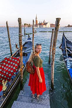 Young woman with red dress on a jetty, Venetian gondolas, in the back church San Giorgio Maggiore, Venice, Veneto, Italy, Europe