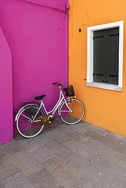 Bicycle leaning against house wall, orange and pink house wall, colorful house wall, colorful facade, Burano Island, Venice, Veneto, Italy, Europe