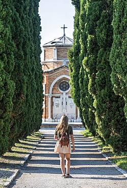 Young woman on the main path of the cemetery island San Michele, Venice, Italy, Europe