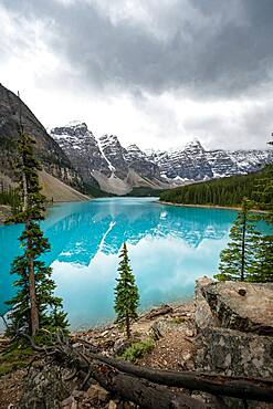Clouds hanging between mountain peaks, reflection in turquoise glacial lake, Moraine Lake, Valley of the Ten Peaks, Rocky Mountains, Banff National Park, Alberta Province, Canada, North America