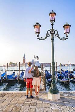 Young couple in front of a jetty, Venetian gondolas, view to church San Giorgio Maggiore, Venice, Veneto, Italy, Europe