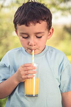 Child little boy drinking orange juice drinking vintage look outside glass, germany