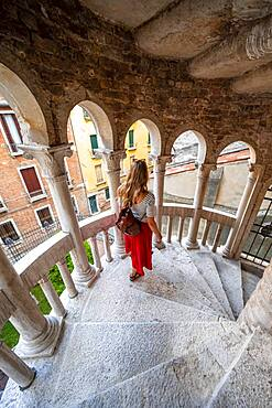 Young woman, tourist at a staircase, of Palazzo Contarini del Bovolo, palace with spiral staircase, Venice, Veneto, Italy, Europe