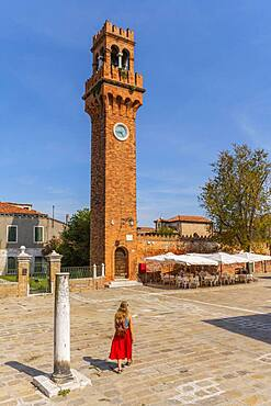 Tourist in red dress in front of St. Stefano bell tower, Murano, Venice, Veneto, Italy, Europe