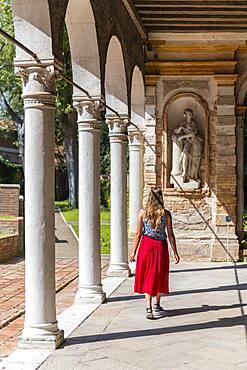 Tourist in red dress in an arcade, Murano Glass Museum, Museo del Vetro, Murano, Murano Island, Venice, Veneto, Italy, Europe