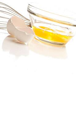 Hand mixer with eggs in a glass bowl on a reflective white background