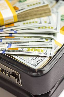 Abstract stacks of newly designed U.S. one hundred dollar bills in briefcase