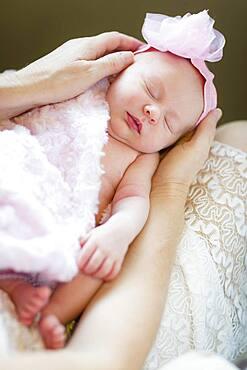 Gentle hands of mother holding her precious newborn baby girl
