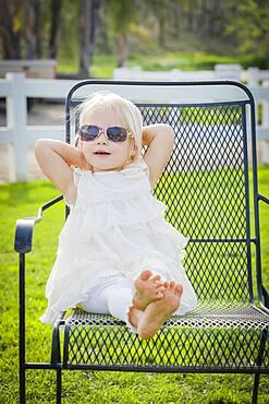 Cute playful baby girl wearing sunglasses outside at the park