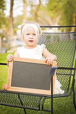 Cute baby girl sitting in chair holding blank blackboard